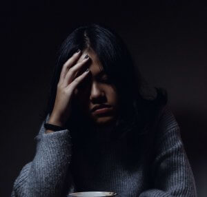 A woman sitting in darkness at a table, holding her head in discomfort with a mug on the table in front of her.