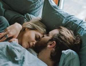 A young couple sleep in each others arms in a bed with blue pillows and blankets.